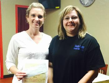 From left: Anna Lee presents donation to Sherry Harding, SC Outreach Ministries Executive Director