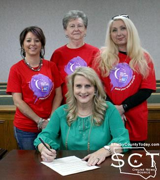 Judge Allison Harbison (seated) signs the proclamation with (from left, standing) Stacy O'Rear, Shirley Brittain, and Kelli Talbert
