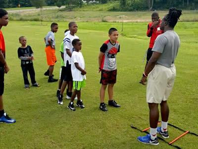 Former Center Roughrider Jeremy Small is seen giving tips to camp participants.