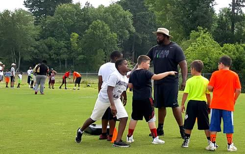 Desmond Hillard is seen on the field instructing campers during the Preston Football Camp.