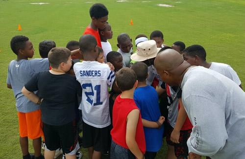 Dwight Preston and John Preston in a huddle with campers.