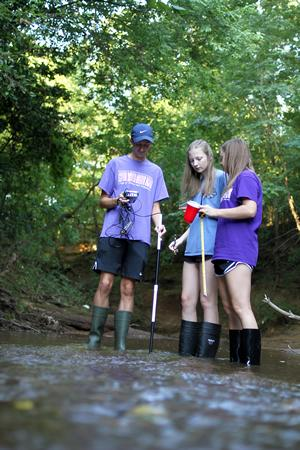 (pictured, from left): Nacogdoches High School seniors Brandon Smith, Marin Beal and Miranda Allbee check the turbidity, take the temperature and measure the depth of the water at Lanana Creek for their Stephen F. Austin State University STEM Academy research project. During their fourth year in the academy, students practice experimental design by conducting their own research.