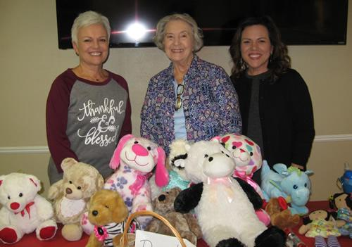 Administrative Assistant, Valerie Warren; program Chairman Linda Anderson; and Executive Director Denise Merriman shown with toys collected by members of the Golden Harvest Ministries Club for the Advocacy Center.