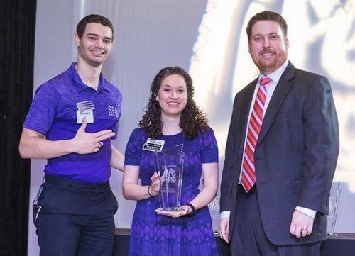 "Collin Rutherford, left, graduate assistant of leadership and service at Stephen F. Austin State University, and Molly Moody, assistant director of student engagement at SFA, accept the Gulf Coast Regional Blood Center award for ""College of the Year"" from Kevin Shipley, director of donor recruitment, at the Celebration of Life luncheon held recently in Houston. According to blood center officials, since 2003, more than 17,000 units of blood have been collected as a result of SFA-hosted drives, saving 50,610 lives. In the days following Hurricane Harvey, a drive on the SFA campus resulted in the donation of more than 150 units of blood."