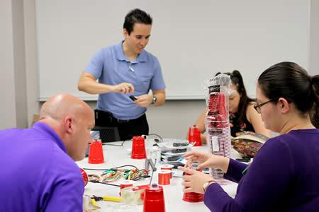 Dr. Hector Ochoa, assistant professor in Stephen F. Austin State University's Department of Physics, Engineering and Astronomy, explains how to use household items to create a speaker during the School of Honors' Maker Fair. The fair was designed to introduce students to various disciplines through hands-on activities.