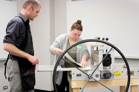 Neal Cox, associate professor in Stephen F. Austin State University's School of Art, supervises as Sydney Wemple, senior English major from New Caney, Texas, makes her first print at the Maker Fair. Students engaged in multiple activities, including a virtual reality demonstration, 3-D printing, making butter and more.