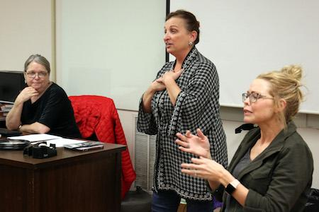Instructor Betty Gruber, left, listens as Anne Stacy-Robbins explains the benefits of Music and Memory, while Lindsey Hines, with Interpreter Training & Consulting Services, provides interpretation for the deaf.