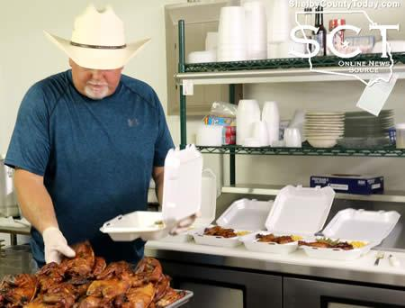 Constable Jamie Hagler is seen preparing chicken plates to deliver to San Augustine.