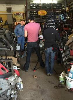 Dennis Leggett (background) in his shop with members of the American Pickers film crew.
