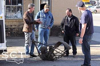 Dennis Leggett (middle) is seen with Mike Wolfe (left) and Frank Fritz (black jacket) and a film crew member (blue shirt) as they discuss an old motorcycle frame in between filming.