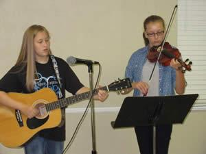 Alana Scull and Hannah Menefee played a number of classical pieces and religious songs for the Golden Harvest Ministries meeting. Hannah played her violin and Alana changed from the violin to a guitar and to a mandolin. Susan Scull came with the girls to care for technical details.