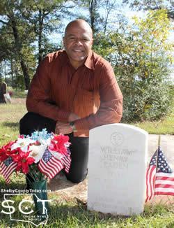 C.J. Eaden kneels by his father's grave marker.