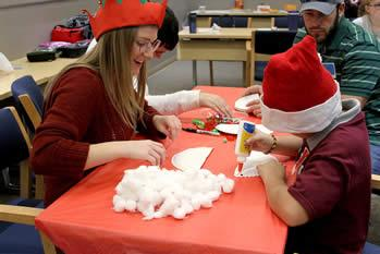 Laura Poynor, Stephen F. Austin State University senior and Braille and Cane Club president, along with SFA student Trenton Rowland help children build Santa beards during a holiday celebration in SFA's Human Services Building.