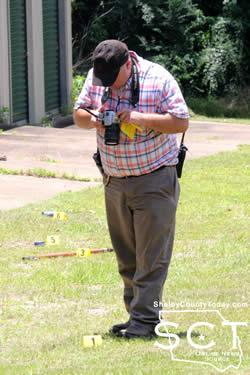 CPD Detective David Haley is seen above photographing evidence markers at the scene