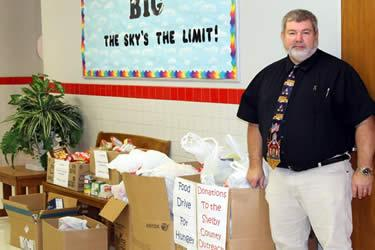 S.W. Carter Elementary Principal Mike Furlow stands beside the food donated by the elementary school.