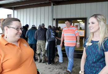 Lauren Hovey (right) visits with Michelle Rodriguez, East Texas Food Bank representative.