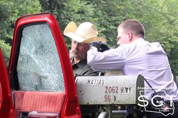 From left: Deputy Roy Bailey and Detective Dickerson measure the passenger window damage.