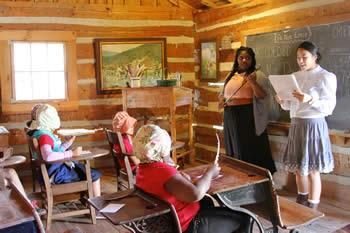 From left: Stephen F. Austin State University elementary education majors Brinisha Shaw and Holly Franz experience life as a teacher in the 1900s as they teach third graders a reading lesson in a one-room schoolhouse at Millard's Crossing Historic Village. This activity was part of the annual Pioneer Days event coordinated by SFA, Millard's Crossing and area schools.