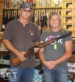Sherryl McGown (right) is seen being presented with her rifle by Glenn Johnson, Shelbyville Lions Club President (left).
