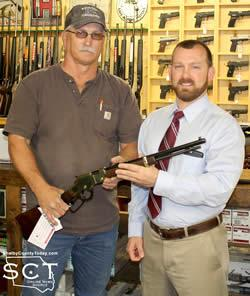 Casey Williams (right) is seen being presented with his rifle by Glenn Johnson, Shelbyville Lions Club President (left).